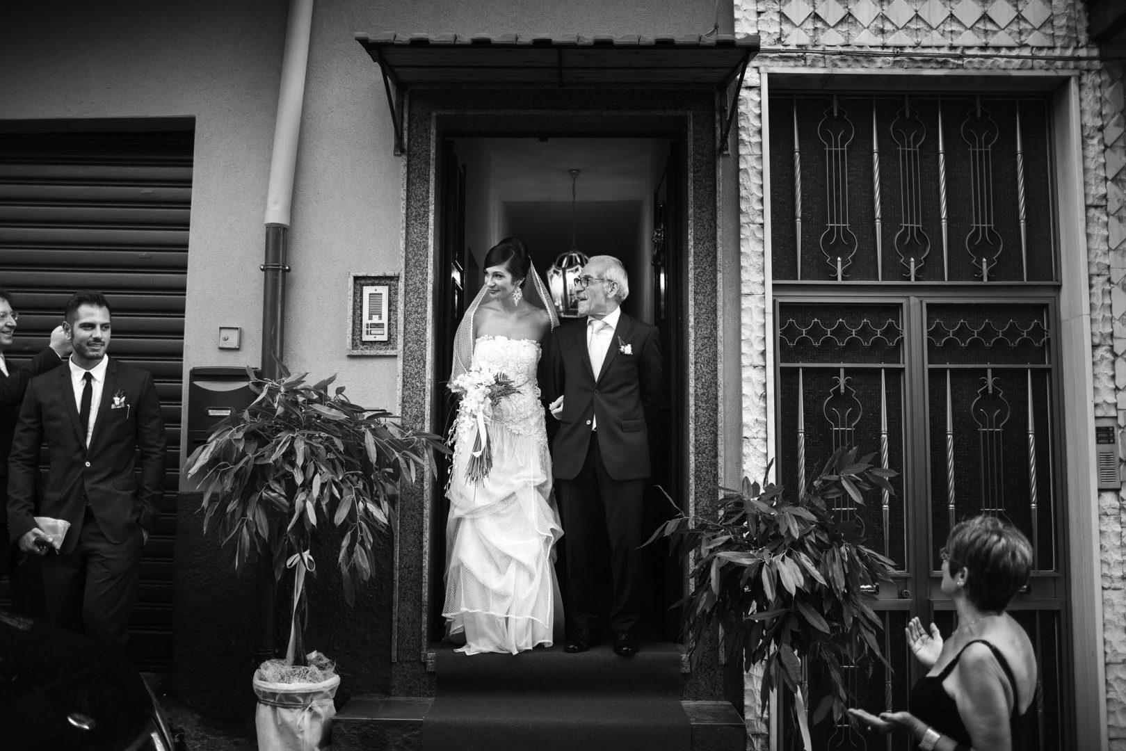 La sposa esce di casa con il papà. Foto di Nino Lombardo