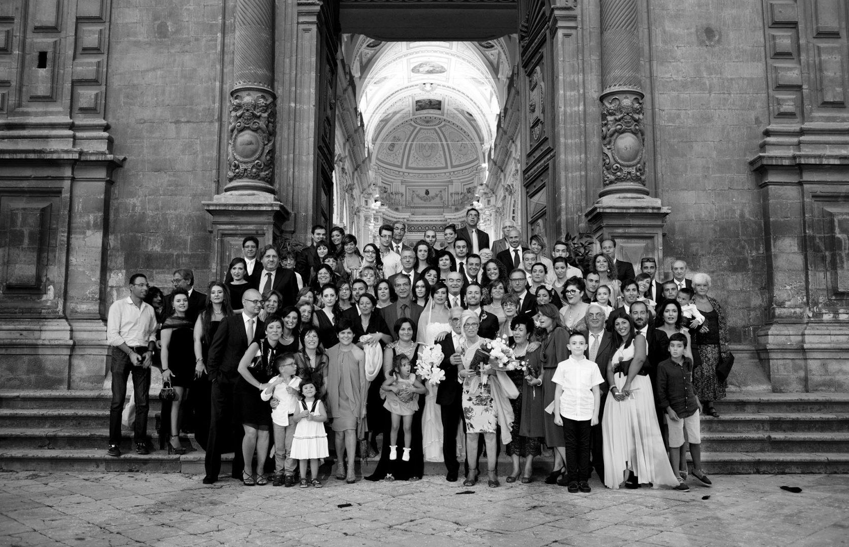 Foto in bianco e nero degli sposi con gli invitati. Nino Lombardo fotografo matrimonio a Modica