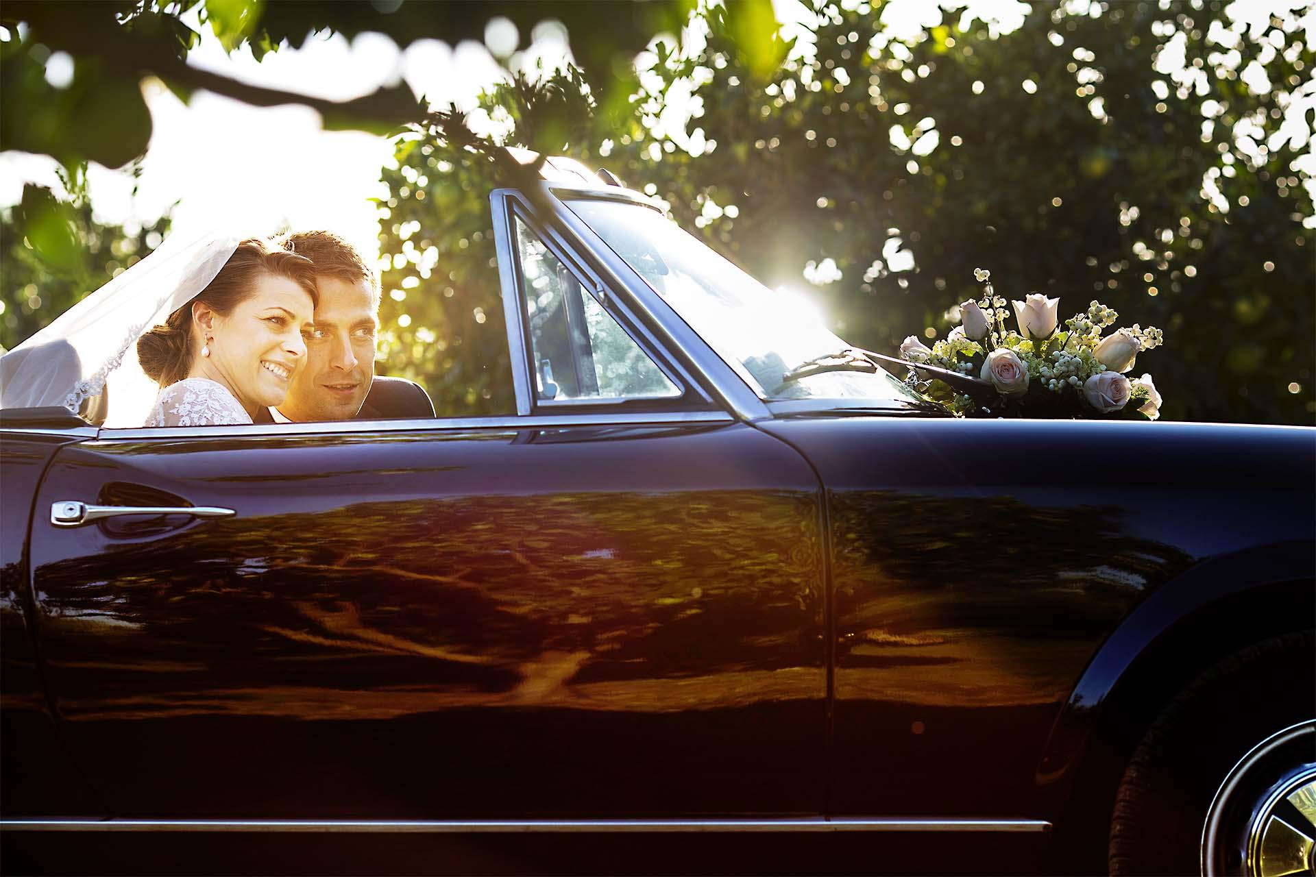 Sposi al tramonto dentro la macchina