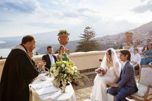 due sposi ascoltano le parole del celebrante del loro matrimonio