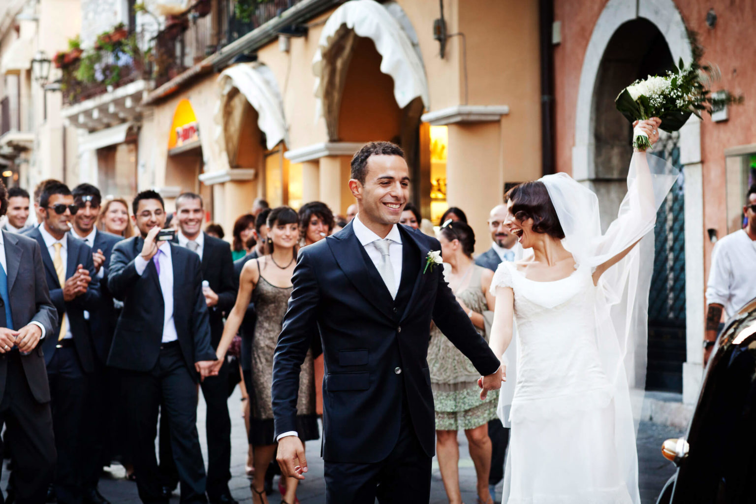 Bride turns cheerful towards friends, wedding photography by Nino Lombardo