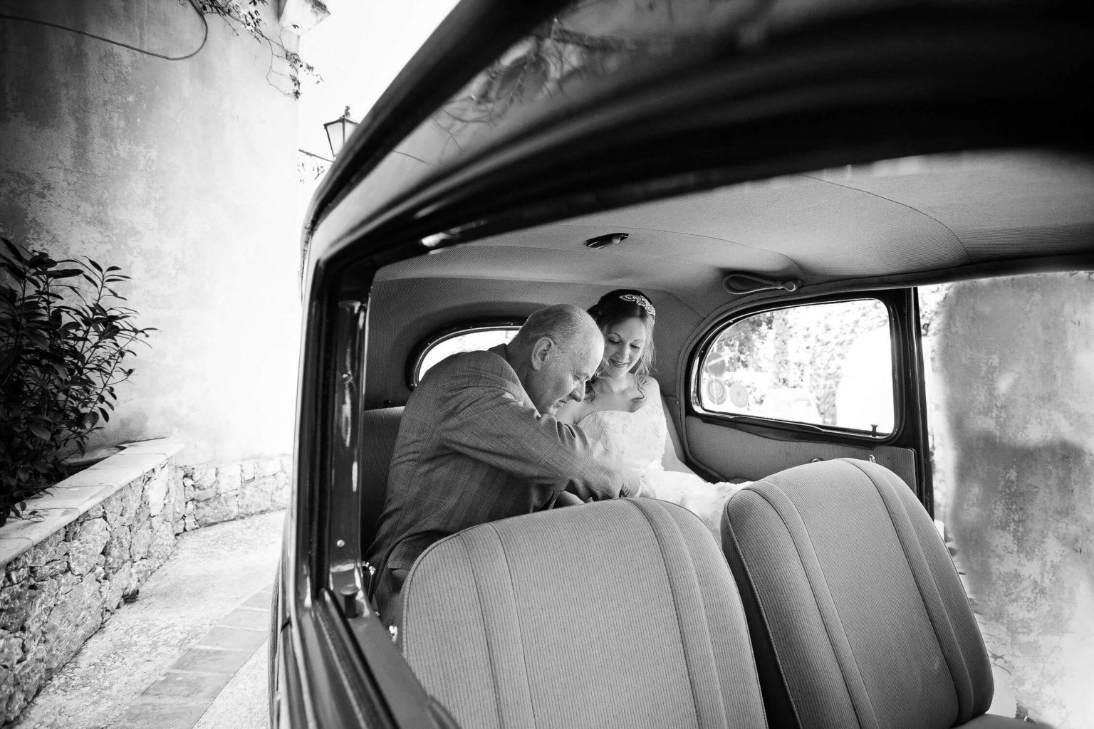 Papà della sposa la aiuta a scendere dall'auto, una foto di matrimonio in bianco e nero di Nino Lombardo