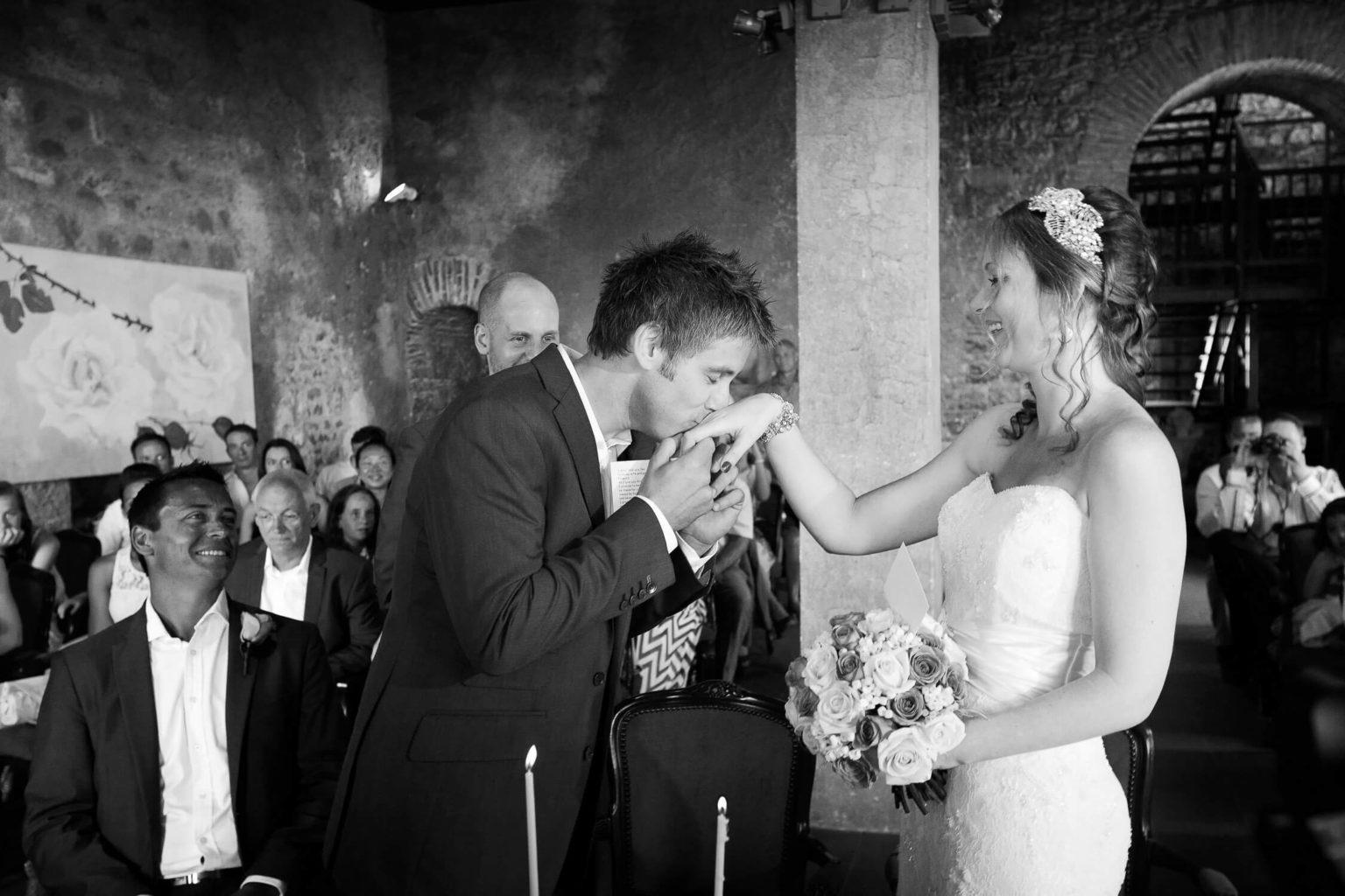 Sposa sorridente mentre lo sposo le bacia la mano in Sicilia,, una foto di matrimonio in bianco e nero di Nino Lombardo