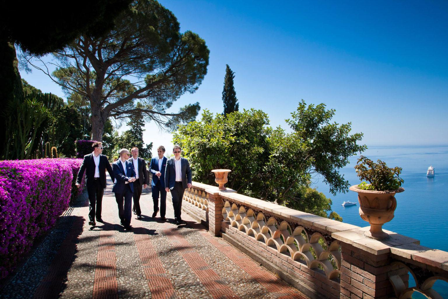 Sposo passeggia con gli amici ai giardini di Taormina, fotografia di matrimonio di Nino Lombardo