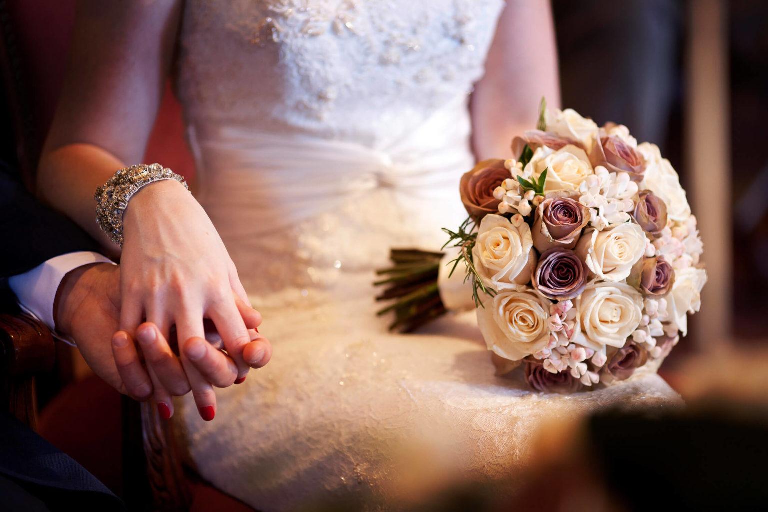 Romantica immagine del bouquet e gli sposi mano nella mano, fotografia di matrimonio di Nino Lombardo