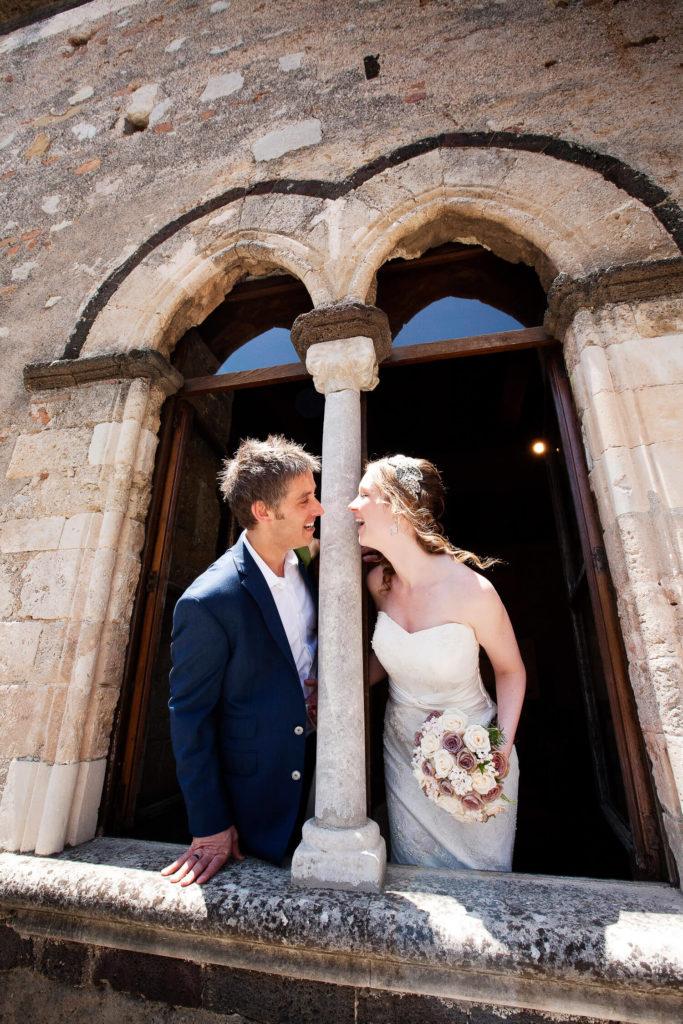 Sorridenti appena sposati alla finestra di Palazzo Duchi, fotografia di matrimonio di Nino Lombardo