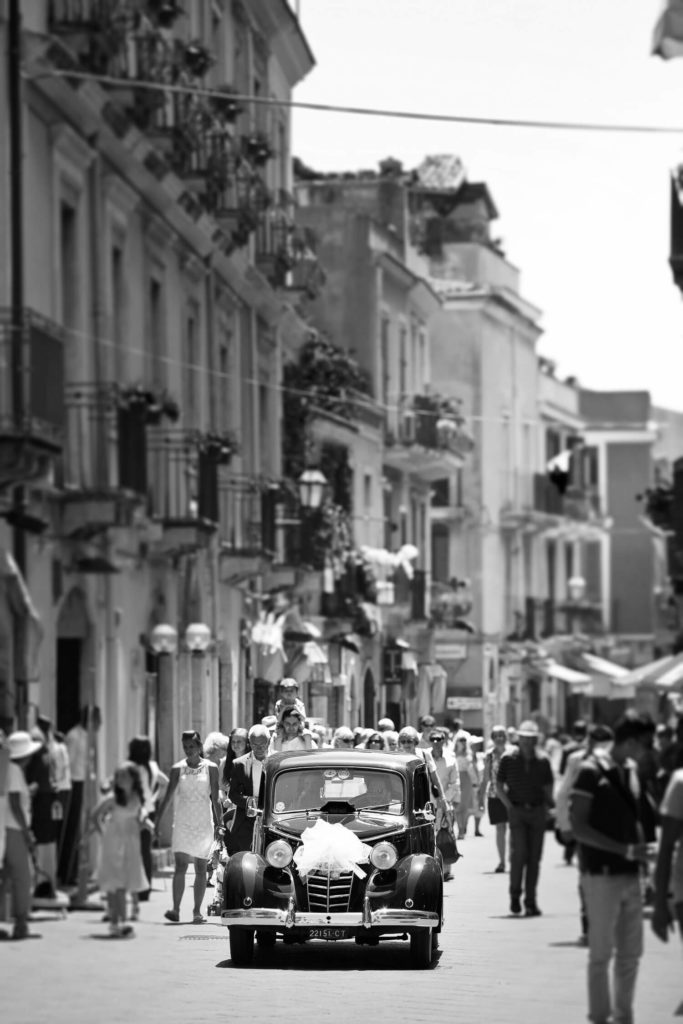 The car of the spouses, a vertical wedding photo in black and white by Nino Lombardo