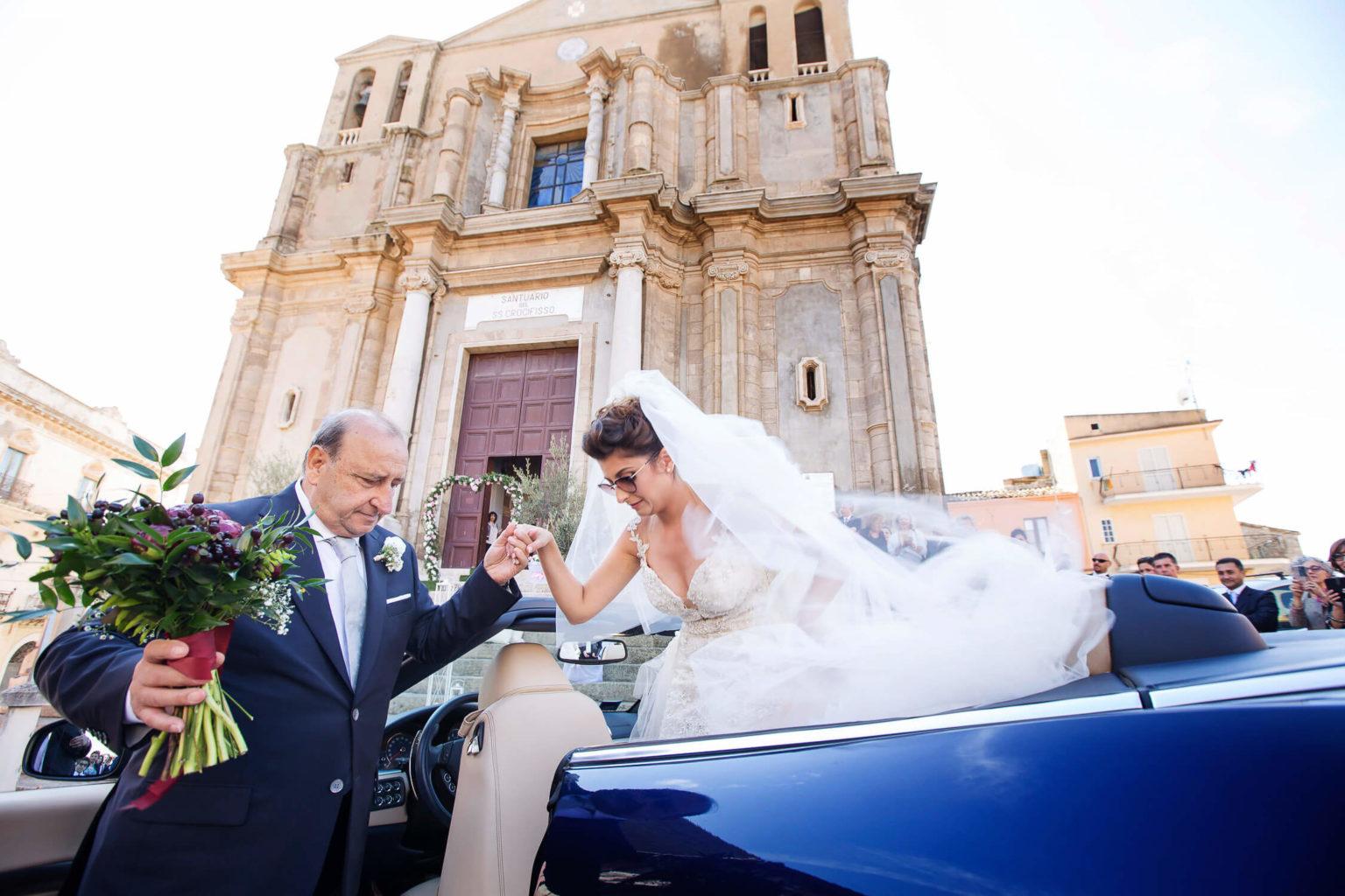 Papà della sposa che le da la mano per scendere dall'auto a Siculiana, foto per matrimoni di Nino Lombardo
