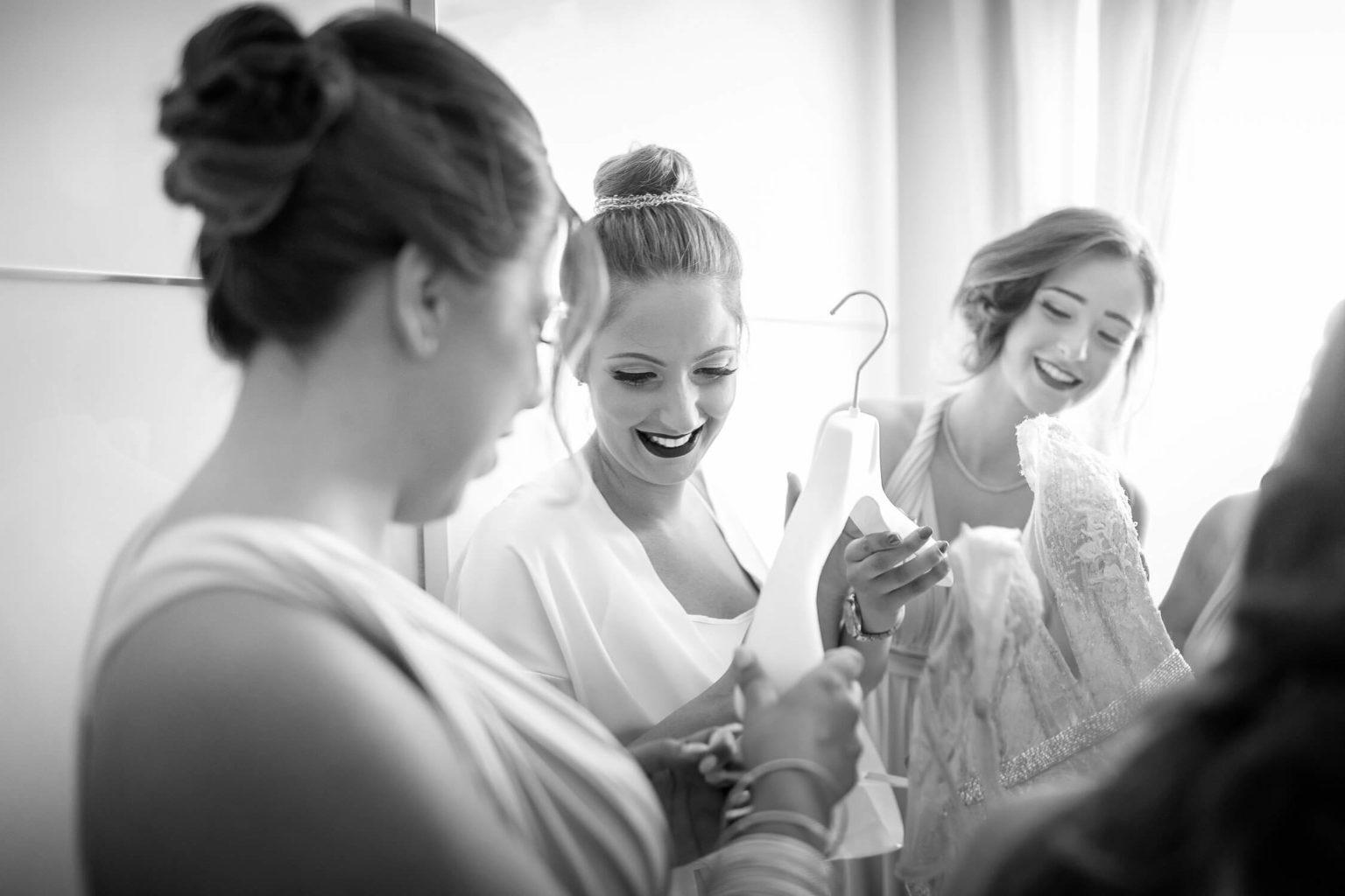 Momenti gioiosi sposa e amiche apprezzano l'abito, foto per matrimonio a Palermo di Nino Lombardo