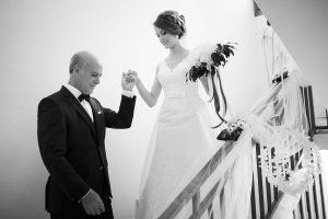 il papà emozionato della sposa fotografato da Nino Lombardo fotografa l'aiuta a scendere le scale della sua casa da nubile, prima di accompagnarla all'altare