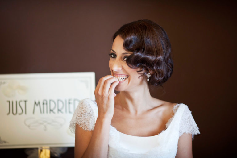 Witty bride laughs with fingernails in her teeth, wedding photography by Nino Lombardo