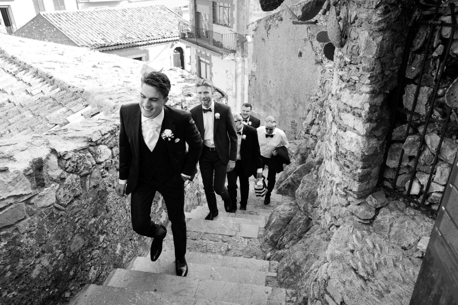 sposo e testimoni si avviano alle Antiche Rovine di Castelmola per la cerimonia di nozze, foto bianco e nero per matrimonio di Nino Lombardo