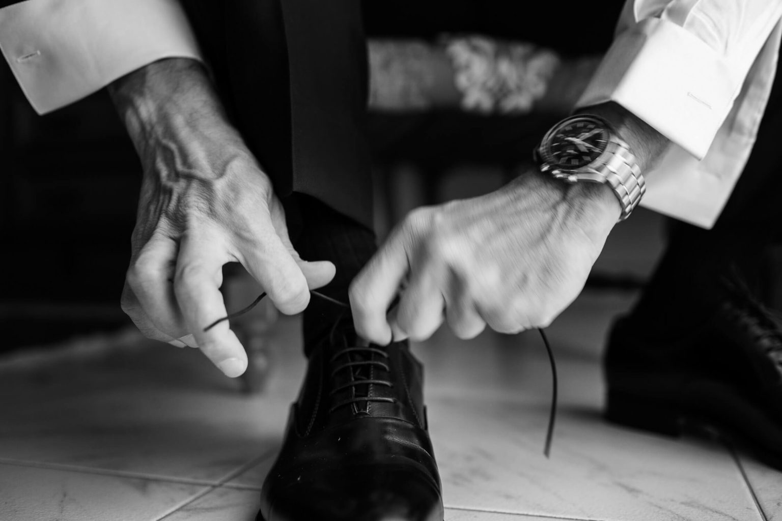 Detail of hands lacing shoes, black and white photography by Nino Lombardo
