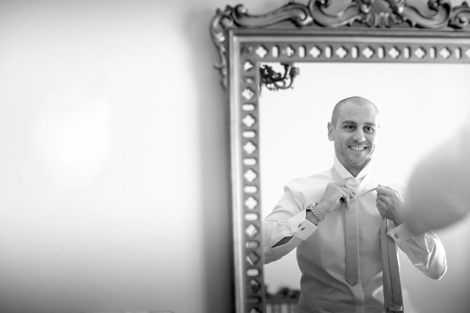 Sposo smiles in the mirror while knotting his tie, a black and white photograph by Nino Lombardo