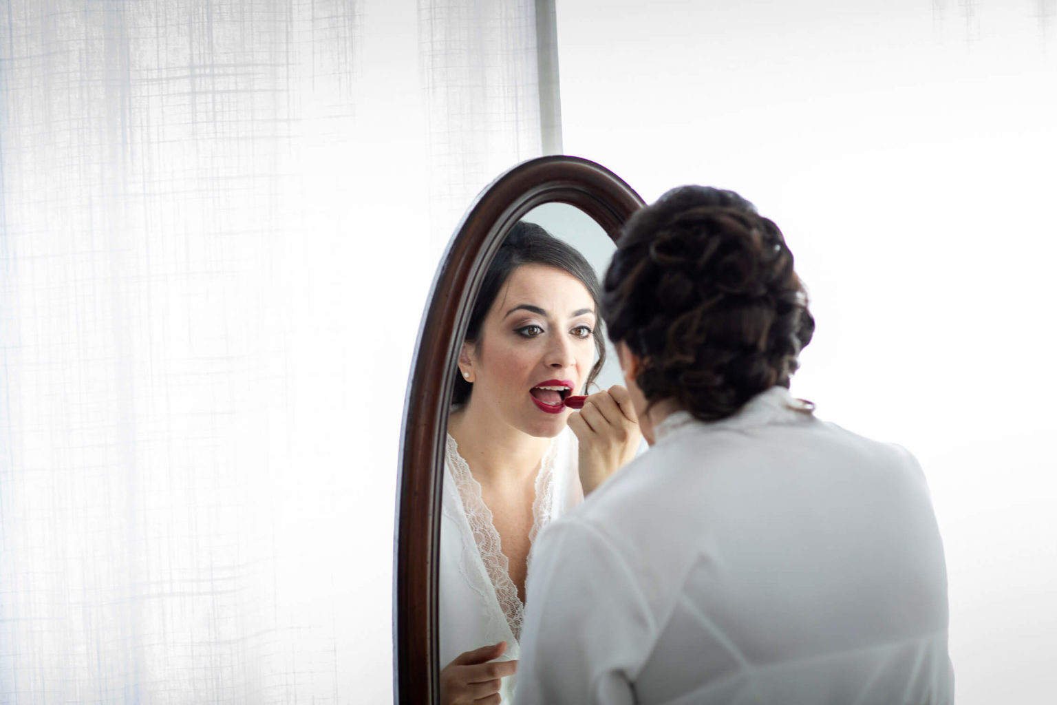 Bride puts on lipstick, photograph by Nino Lombardo