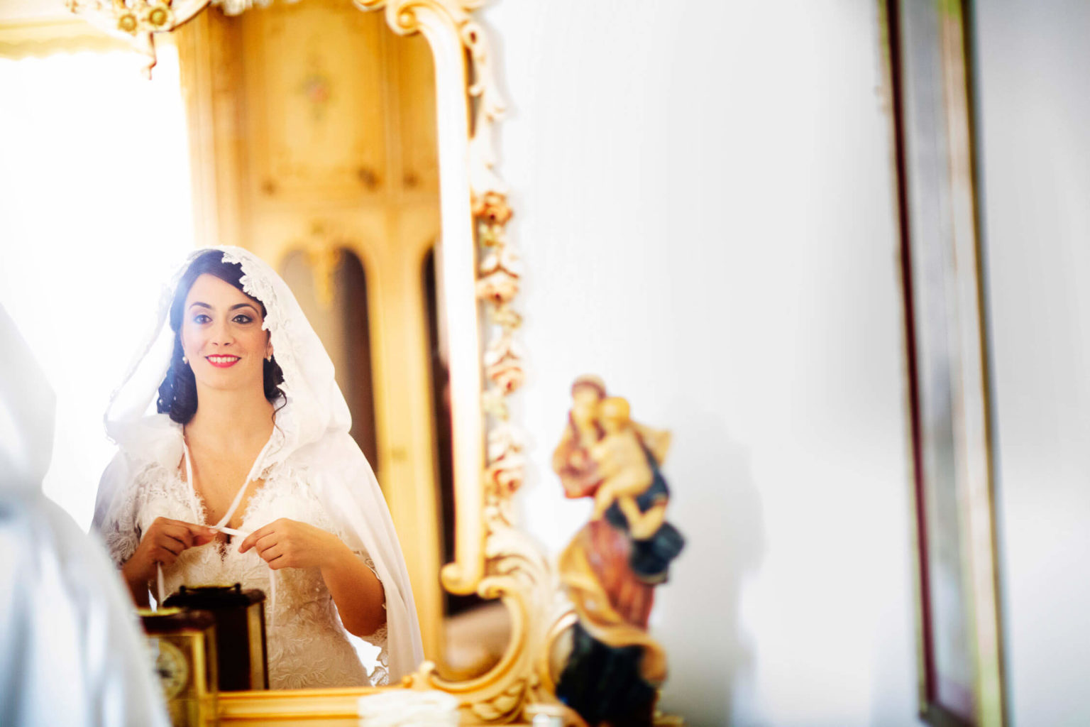 Bride looks at herself in the mirror, photograph by Nino Lombardo