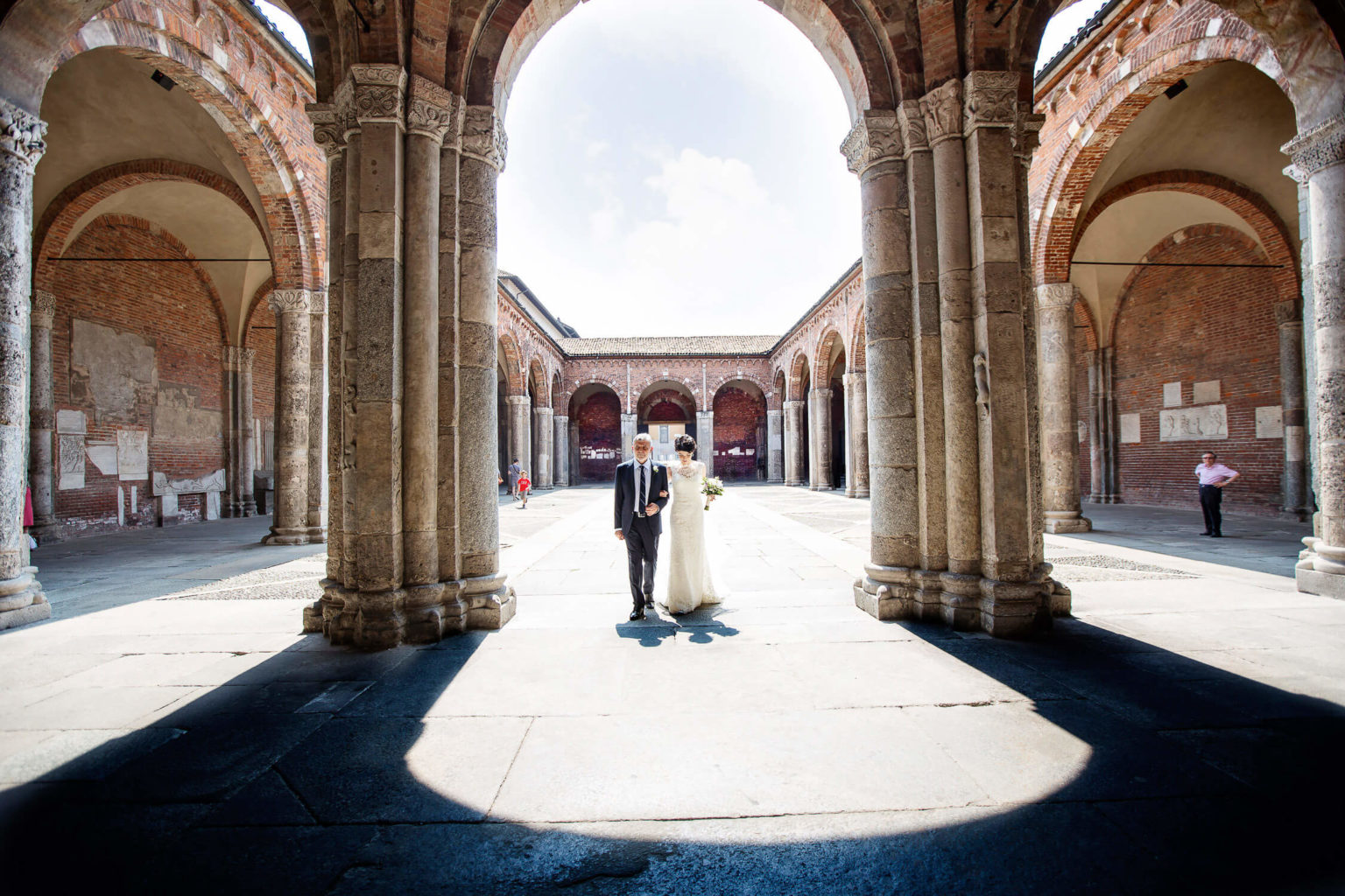 The bride arrives with her dad, a beautiful view of the Basilica of Sant'Ambrogio in Milan, wedding photos by Nino Lombardo