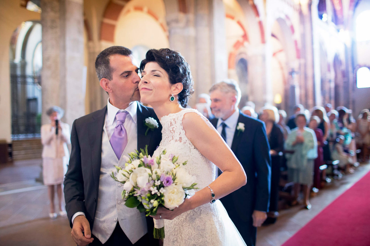 Bride happy to receive a kiss from her husband at the Basilica of Sant'Ambrogio in Milan, wedding photo by Nino Lombardo