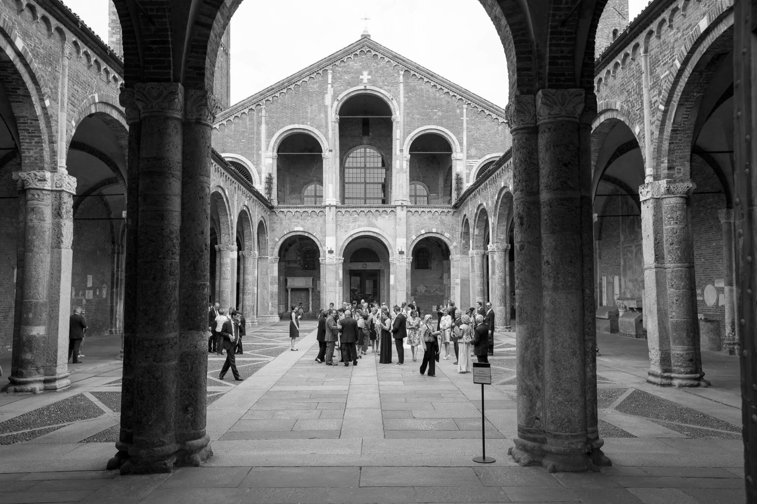 Spouses and guests exchange greetings at the Basilica of Sant'Ambrogio in Milan, a wedding photo by Nino Lombardo