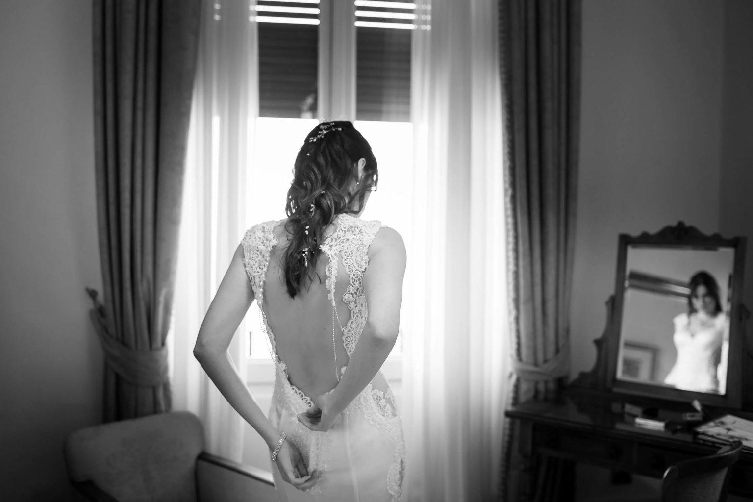 Bride while closing the dress at the San Domenico Palace for wedding in Taormina, wedding photos of Nino Lombardo