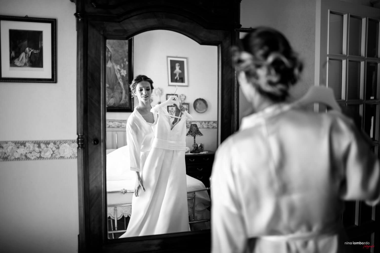 Sposa ammira il suo abito del fotografo matrimonio Trapani in Sicilia