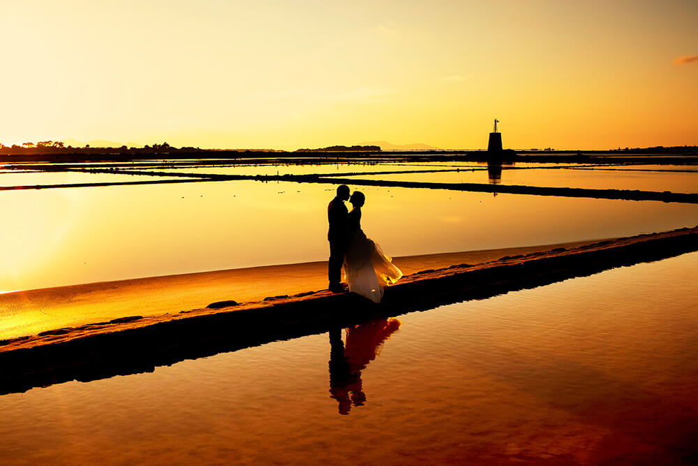 Beautiful photo of a wedding with sunset at the salt pans of Trapani