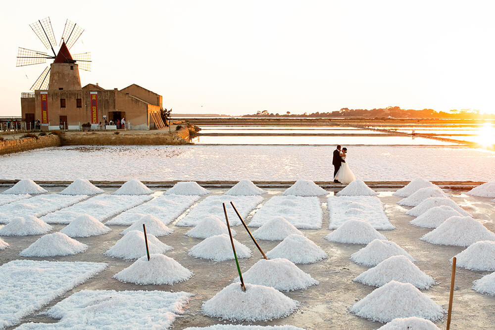 The spouses photographed by the wedding photographer Nino Lombardo at sunset at the salt pans of Trapani